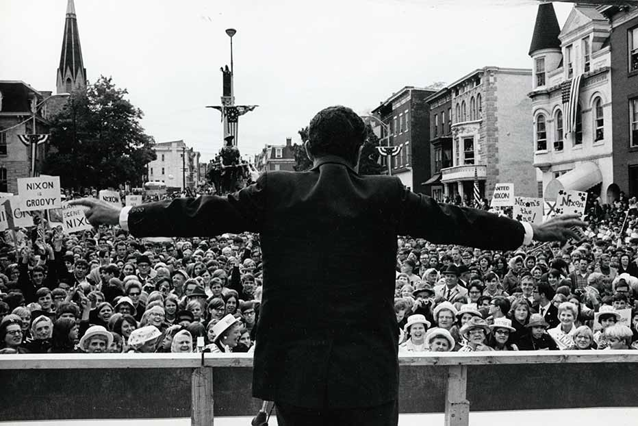 Richard Nixon extends his arms as he addresses a crowd at a campaign rally in 1968